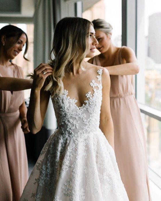 Novia probándose vestidos en compañía de amigas