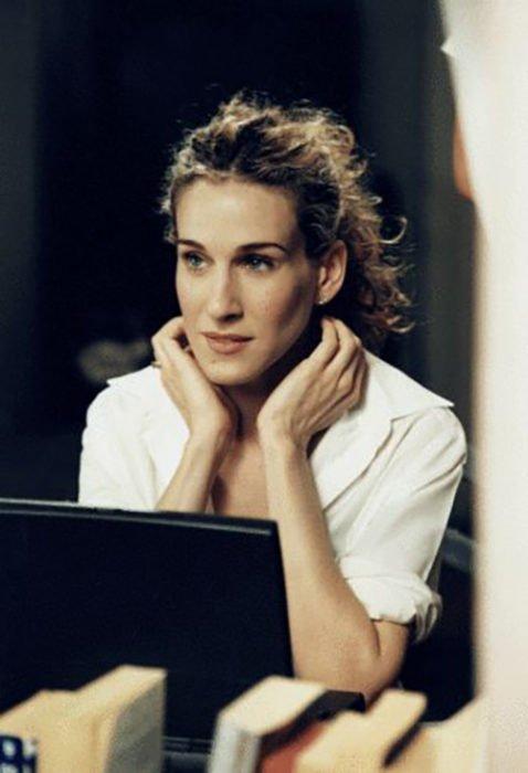 Carrie Bradshaw frante a su computadora usando una blusa blanca y cabello recogido en una coleta alta