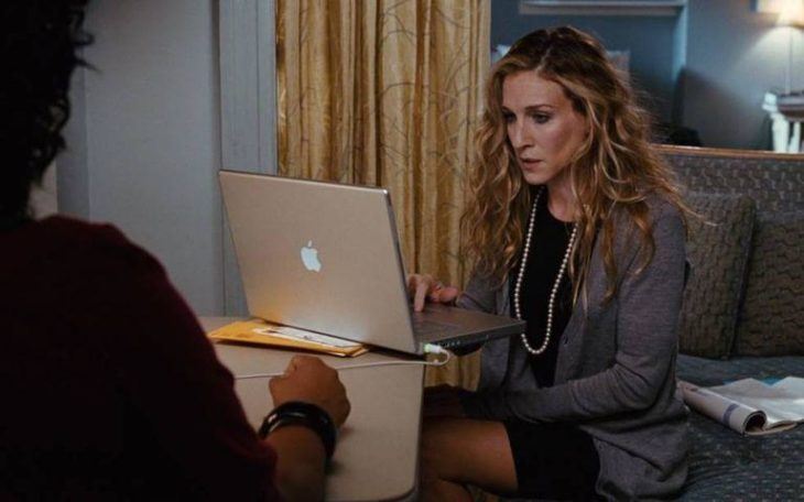Carrie Bradshaw con saco formal escribiendo en su laptop mac