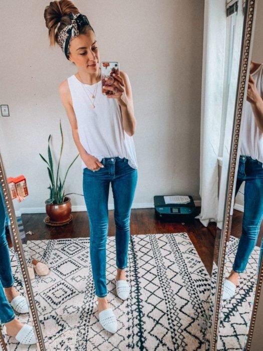 Chica usando skinny jeans, blusa blanca y alpargatas
