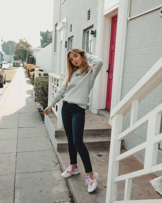 Chica usando unos skinny jeans con sueter de color blanco y tenis