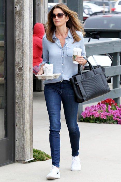 Chica usando skinny jeans con una camisa de color mezclilla y tenis blancos