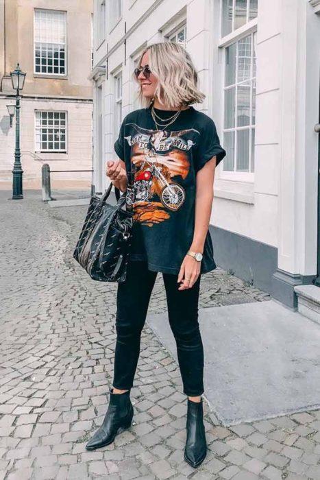 Chica usando unos skinny jeans y camiseta de rock con botines