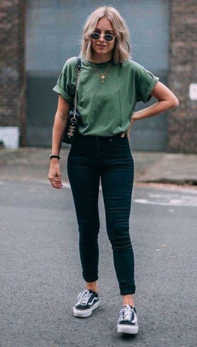 Chica usando skinny jeans de color negro y blusa de color verde