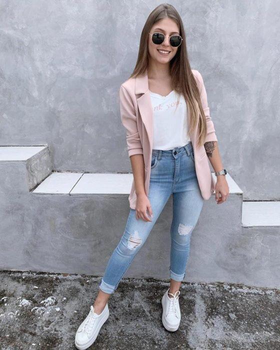 Chica usando unos skinny jeans, tenis blancos, blazer rosa y camisa blanca