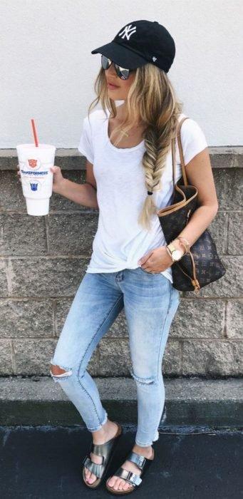 Chica usando skinny jeans con blusa blanca y gorra de beisbolista