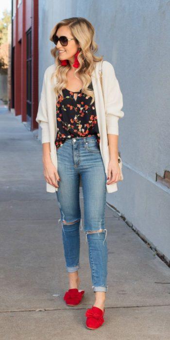 Chica usando skinny jeans con zapatos de color rojo, blusa negra y cardigan blanco
