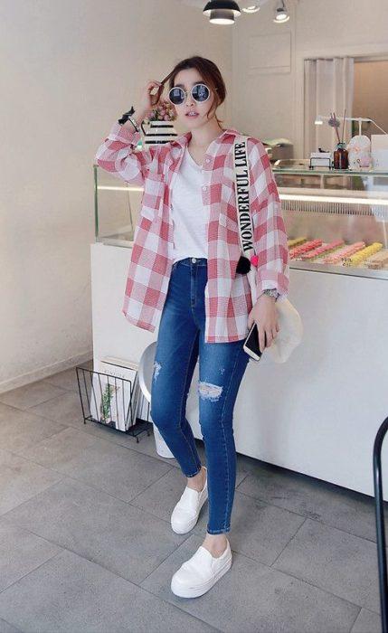Chica usando unos skinny jeans con una camisa de color blanco y camiseta de cuadros