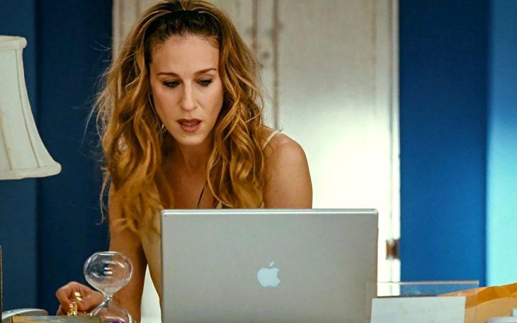 Carrie Bradshaw trabajando frente a computadora mac
