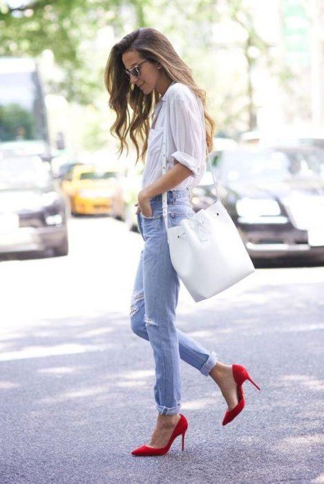 Chica con jeans y blusa blanca con tacones pump rojos