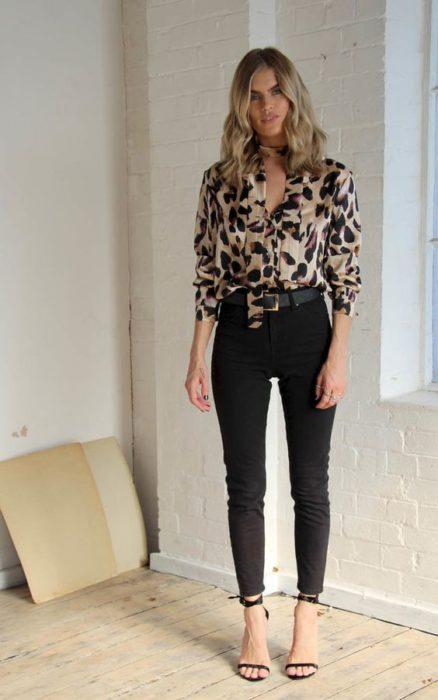 Chica rubia con blusa de leopardo, pantalón negro y sandalias de tacón negras