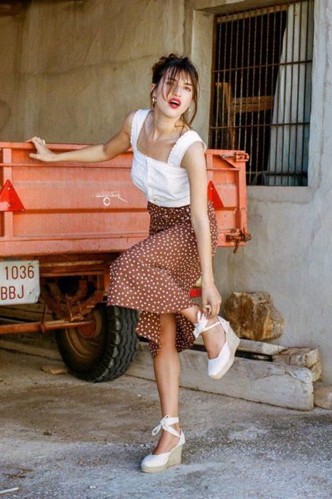 Chica con falda larga de flores y blusa blanca con tacones de cuña