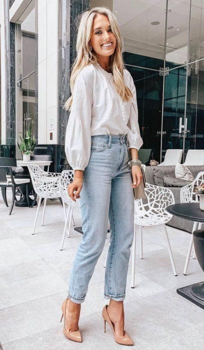 Chica rubia con jeans, blusa blanca y tacones nude