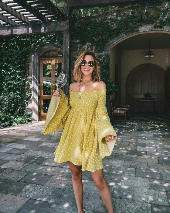Chica usando un vestido holgado de color amarillo con mangas anchas