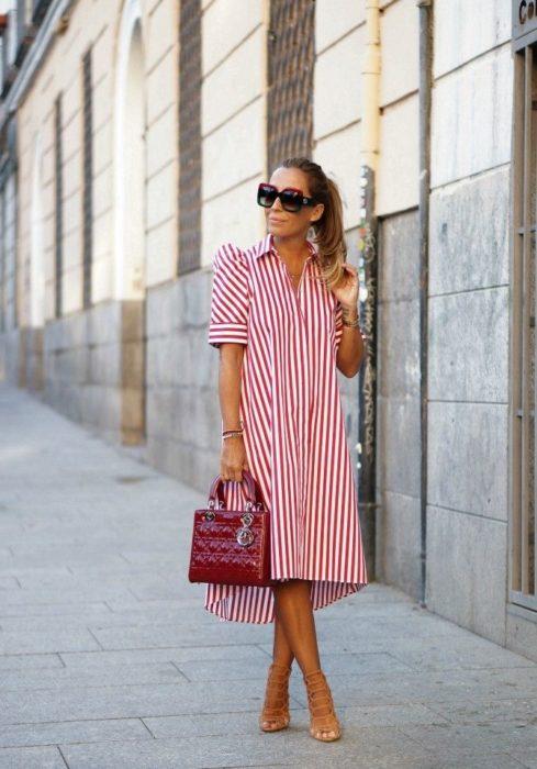 Chica usando un vestido holgado de color rojo con líneas blancas