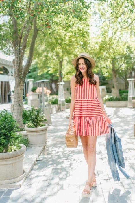 Chica usando un vestido holgado de color blanco con líneas rojas