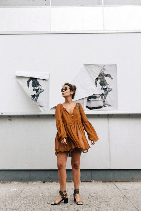 Chica usando un vestido holgado de color café de mangas anchas