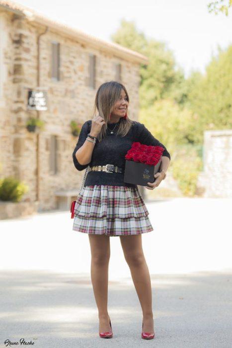 Chica posa con blusa negra y falsa de cuadros color blanco con rojo