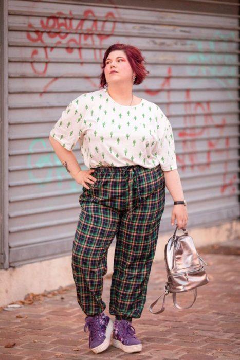 Chica curvy se pone la mano en la cintura y posa con blusa blanca con estampado de cactus y pantalón verde de cuadros