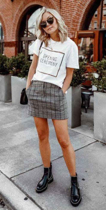 Chica rubia de cabello suelto pone las manos dentro de los bolsillo de su falsa color gris con cuadros y usa una blusa blanca y botines negros