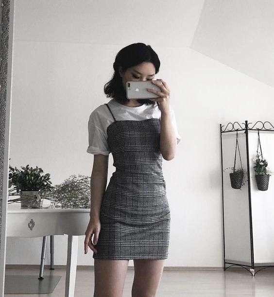 Chica se toma una foto frente al espejo con blusa blanca y vestid pegado de cuadros color gris