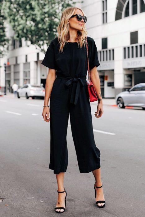 Chica rubia con total look negro y bolso rojo