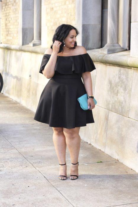 Chica curvy usando un vestido de corte hasta las rodillas y escote off the shoulders