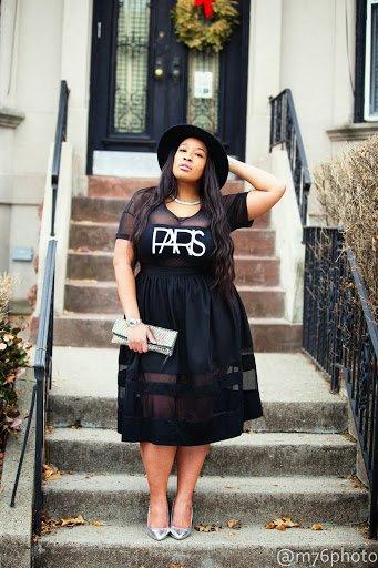 Chica curvy con un vestido de colr negro con un sombrero y clutch de color gris
