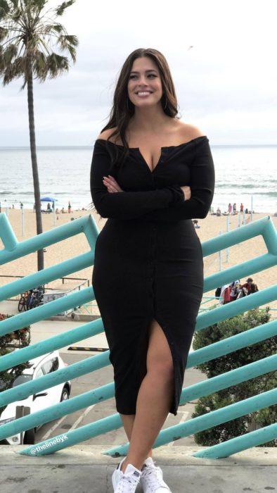 Chica curvy con un vestido de color negro de escote corazón y hombros descubiertos