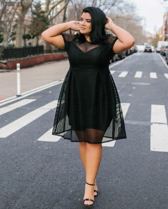 Chica currvy usando un vestido de color negro con transparencias
