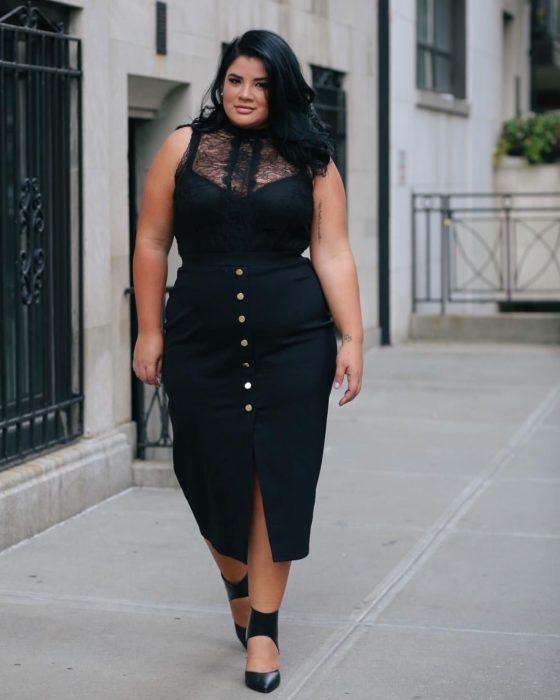 Chica curvy con un vestido negro de botones y encaje en el pecho de color negro