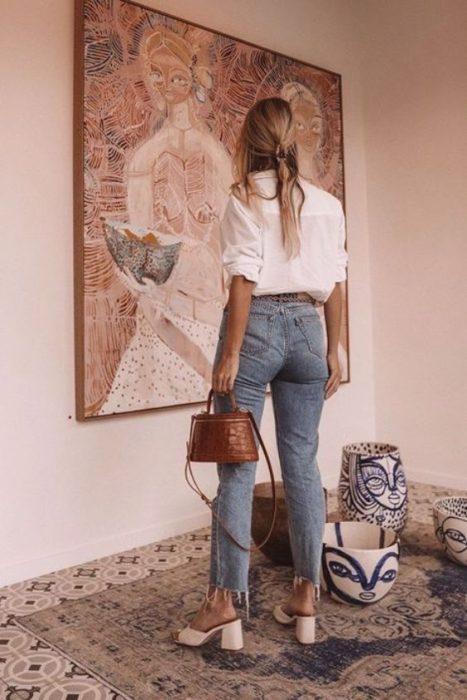 Chica de espaldas mira un cuadro y usa blusa blanca, jeans y tacones cuadrados