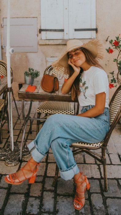 Chica sentada recarga su cara en su brazo usa pantalón de mezclilla y zapatos naranjas cuadrados