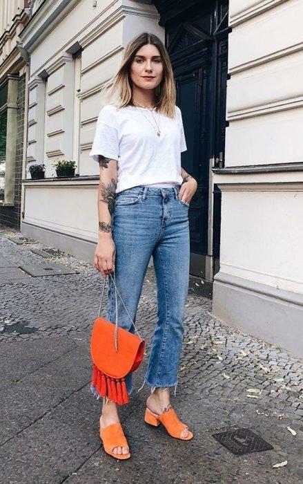 Mujer viste blusa blanca, jeans y bolsa y zapatos naranjas con tacón cuadrado