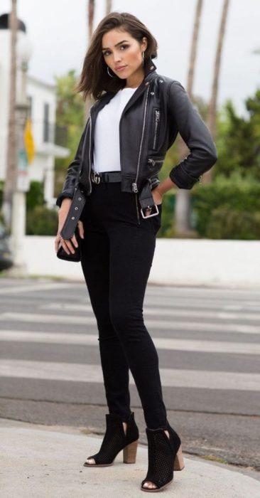 Olivia Culpo con pantalón negro, chamarra tipo cuero rockera y botines descubiertos de la parte de adelante color negros