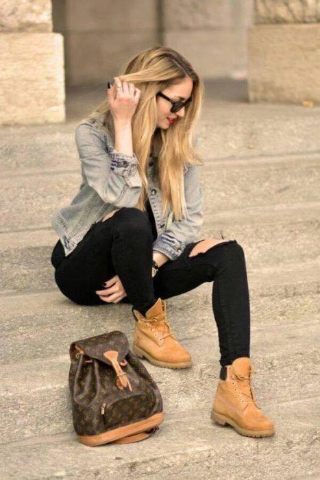 Mujer rubia sentada en escalones se toca el cabello con la mano derecha y viste pantalón negro, chamarra de mezclilla y botas tipo tomberland color camel
