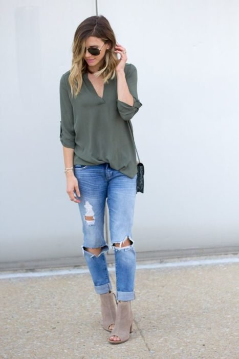 Chica rubia con blusa verde militar y jeans rotos con botines grises