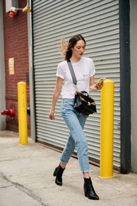 Chica camina por la calle vistiendo jeans, blusa blanca y botines negros