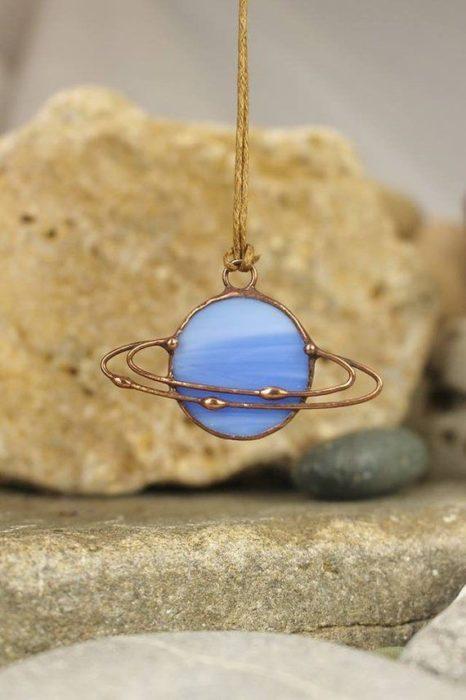 Collar inspirado en el universo con cadena dorada y Saturno en color azul bebé