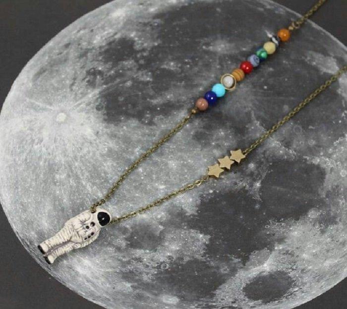 Collar inspirado en el universo con el sistema solar, algunas estrellas y un astronauta