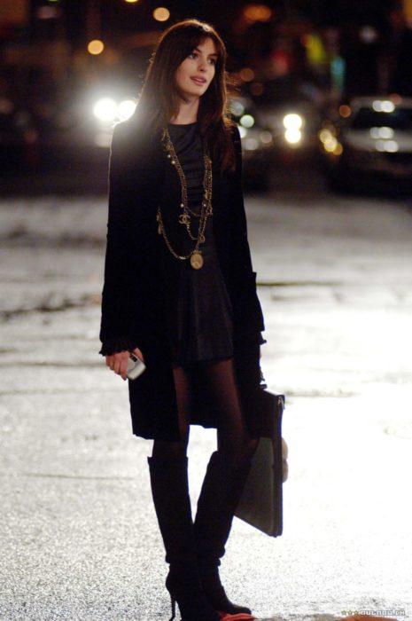 Escena de la película El Diablo Viste a la moda. Andrea usando un atuendo en negro mientras posa para una fotografía