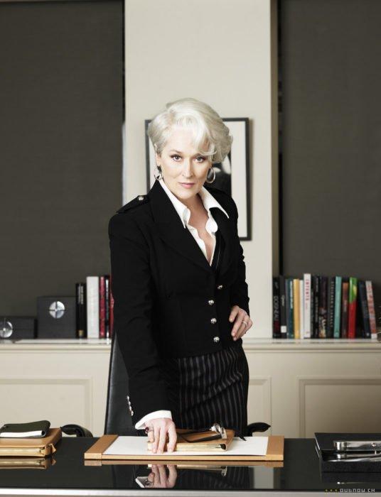 Escena de la película El Diablo Viste a la moda. Miranda en su oficina usando un atuendo elegante de color negro