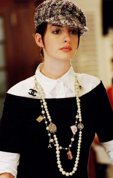 Escena de la película El Diablo Viste a la moda. Andrea usando un suéter de color negro con una blusa blanca y un collar de chanel