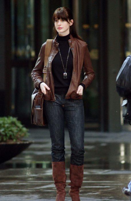 Escena de la película El Diablo Viste a la moda. Andrea usando un look de jeans, botas y chaqueta mientras esta parada en una calle