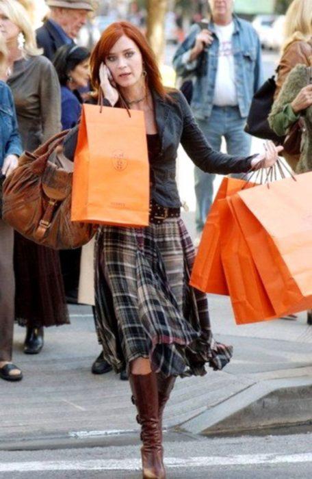 Escena de la película El Diablo Viste a la moda. Emily camiando por la calle sosteniendo varias bolsas en las manos