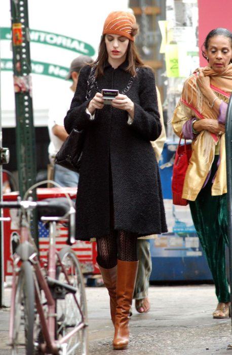 Escena de la película El Diablo Viste a la moda. Andrea caminando por la calle mientras usa un abrigo negro, botas y un sombrero de color naranja
