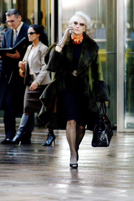 Escena de la película El Diablo Viste a la moda. Miranda caminando por las calles mientras usa un abrigo de color verde