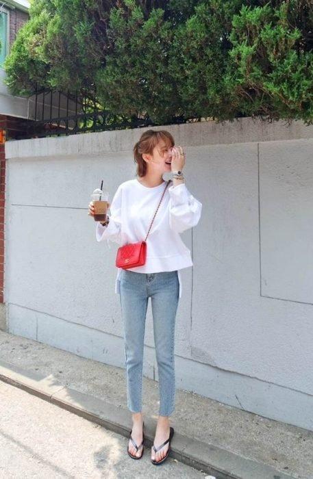 Chica de cabello corto sostiene una coca cola y usa jenas, sudadera blanca y flip flops