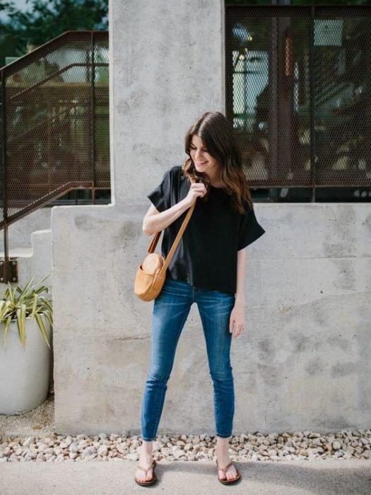 Chica camina en la calle con jeans, blusa negra y flip flops