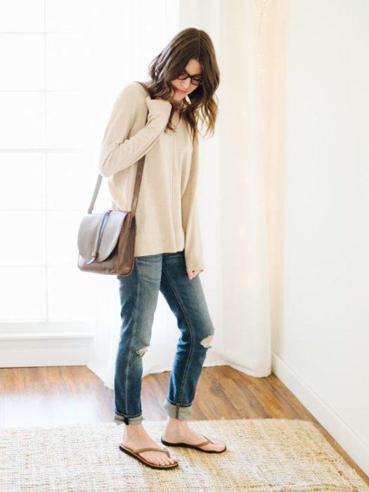 Chica con sudadera larga blanca, bolsa café, jeans y flip flops